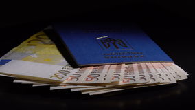 Money and passport on the table. Euro banknote in the passport are rotated on the black desk stock video