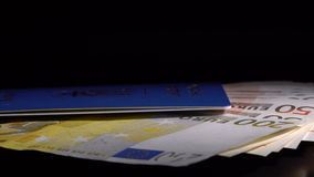 Money and passport on the table. Euro banknote in the passport are rotated on the black desk stock video footage