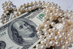 Money for pearls. Elegant pearls and money stock images