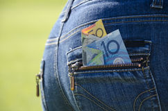 Money peeping out of a blue jeans back pocket Royalty Free Stock Photography