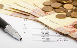 Money, pen and document. Ukrainian banknotes and coins laid out on document with pen Royalty Free Stock Images