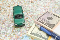 Money, pen and green car on map Stock Image