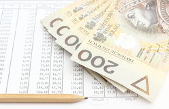 Money and pencil lying on spreadsheet Stock Image