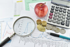 Money, pencil, magnifier, apple and calculator placed on documen Royalty Free Stock Images