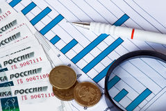 Money, pencil and magnifying glass on a blue graph Stock Photos
