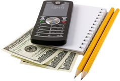 Money,phone. Isolated dollars, phone and notebook Royalty Free Stock Image