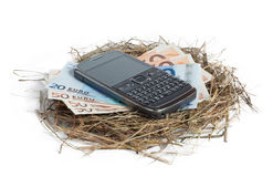 Money and phone in nest. Isolated on white Royalty Free Stock Photo