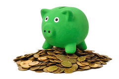 Money and Piggy Bank. Green piggy bank on coins stack isolated on white Stock Photo