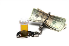 Money, pill bottel, and Handcuffs Royalty Free Stock Images