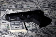 Money & Pistol. Criminal business. Black gun on 100-bucks background. Hard direct light. Clos-Up studio shot Stock Photo