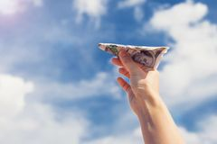 Money plane on the fingers over sky with clouds royalty free stock photography