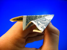 Money Plane in Hand. A hand holds a paper airplane made of money royalty free stock photos
