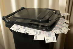 Money in a plastic garbage bin Royalty Free Stock Images