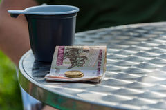 Money and the plastic mug on the edge of the table. Royalty Free Stock Photo