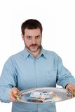 Money on a Plate. Young man holding paper euros on a silver plate Royalty Free Stock Images