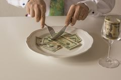 Money on a plate being cut like food with a knife and fork. By two human hands Stock Photos