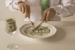 Money on a plate being cut like food with a knife and fork. By two human hands Stock Photo