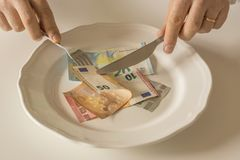 Money on a plate being cut like food with a knife and fork. By two human hands Royalty Free Stock Photos