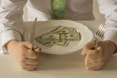 Money on a plate being cut like food with a knife and fork. By two human hands Royalty Free Stock Photography