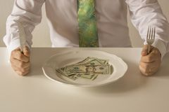 Money on a plate being cut like food with a knife and fork. By two human hands Royalty Free Stock Images