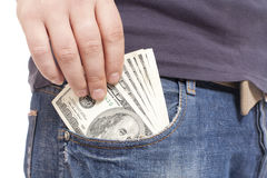 Money in the pocket. Human hand is putting money in the pocket Royalty Free Stock Photography