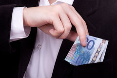 Money into pocket. Businessman putting money into his pocket Royalty Free Stock Photos