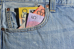 Money in the Pocket. Australian money in the front pocket of a pair of jeans, $50, $20 and $5.00. Copyspace royalty free stock image