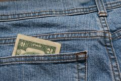 Money in pocket. Two dollar bill in jean pocket Royalty Free Stock Image