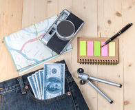 Money in pocket jean ,camera and map Royalty Free Stock Image