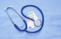Money in the pocket of a medical uniform and stethoscope Royalty Free Stock Image
