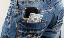 Money in a pocket. Money and mobile phone in a hip-pocket of trousers stock photography
