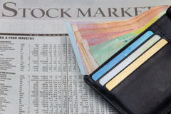 Money in a pocket over stock market newspaper background Royalty Free Stock Images