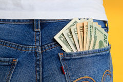 Money in pocket, rear view. Yellow background Stock Photo