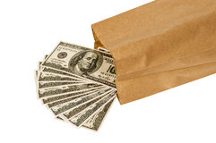 Money Pouring Out Of Brown Paper Lunch Bag. Horizontal shot of hundred dollar bills pouring out of a paper lunch bag.  Concept of saving money by brownbagging or Royalty Free Stock Image