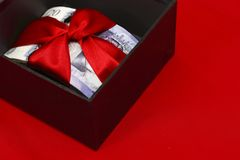 Money prize in black box. Stack of english cash with red ribbon in black open gift box isolated on red background Stock Image