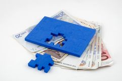 Money Problems. A puzzle lying on top of various bank notes symbolizing money issues with the final part of the solution in sight Stock Photos