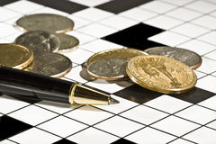 Money Problems. Executive's ballpoint pen and coins on a blank crossword puzzle.  Conceptual image for money problems, problem solving, brain storming, etc Royalty Free Stock Image