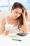 Money problems. Vertical shot of a disappointed girl counting money at home Stock Photo