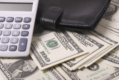 Money, purse and calculator. Paper money dollar banknotes black purse and calculator Royalty Free Stock Photography