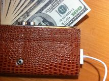 The money in the purse on the charging. Money in the wallet, a stack of dollars, paper money in the wallet stock photos
