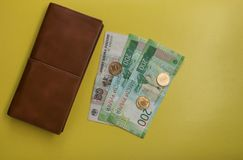 Money with a purse lying on a yellow background stock images