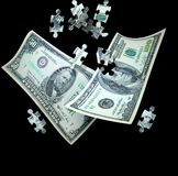 Money puzzle. A 100 and 50 dollar bill float down with puzzle pieces falling into place. Concept for business or finance solutions or success stock photography