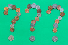 Money Questions. Coins forming three question marks on green background Stock Image