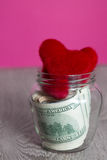 Money and red hearts. Dollars in open jar on grey wooden background.  Copy space. Love. Valentine day. Stock Photos