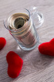 Money and red hearts. Dollars in open jar on grey wooden background.  Copy space. Love. Valentine day. Royalty Free Stock Photo