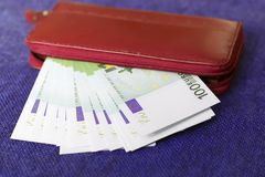 Money in a red purse on a blue background. The money in a red purse on a blue background Royalty Free Stock Image