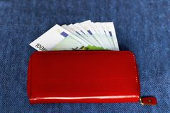 Money in a red purse on a blue background. The money in a red purse on a blue background Stock Photography