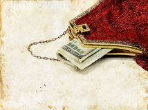 Money in Red Purse on Grunge Background. Hundred dollar bill sticking out of a red beaded purse. Grunge background Stock Photos