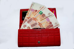 Money in a red purse. Russian rubles in the red purse on a white background, three banknotes of five thousand stock photo