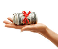 Money with red ribbon in womens hand. Royalty Free Stock Images